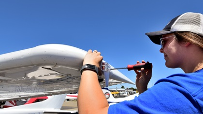 Kaitlyn Jones, an airframe and powerplant mechanic for Five Rivers Aviation, an FBO at Livermore Municipal Airport, installs a wingtip ADS-B unit during AOPA's Livermore Fly-In. Five Rivers installed several units on aircraft that had flown in for the event. Photo by Mike Collins.