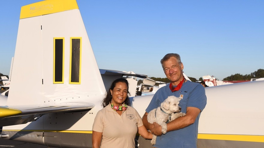 Mitzi Saylor and her husband and co-pilot, Dave Saylor (holding Millie, their Maltese mix), stand beside the Van's Aircraft RV-10 in which they won the 2020 Hayward Air Rally. Photo by Carl La Rue.