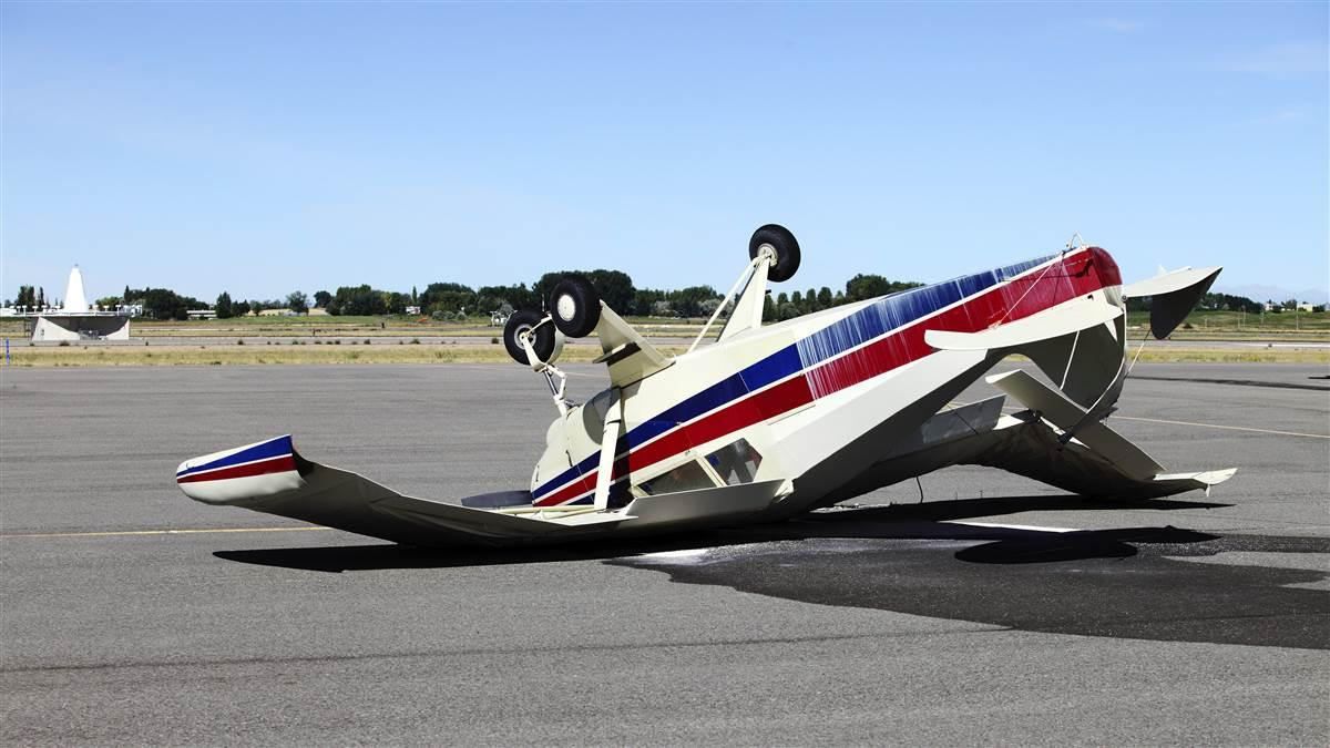 An mangled airplane resting upside down on the tarmac