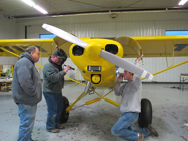 After Baker Air Service's Darin Meggers runs the Super Cub's Lycoming O-320 engine for a few minutes, he shuts and down and brings it back inside for the crew to inspect the engine compartment for oil leaks.