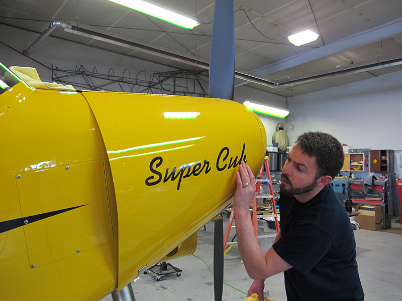 Aerotronics technician Isaac Horn applies the Super Cub decal with expert precision.