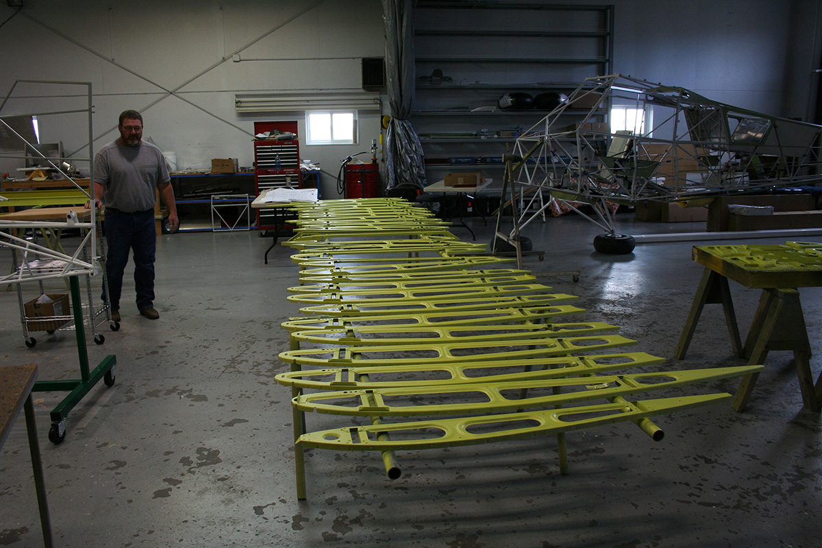 The wing ribs are painted yellow and then laid out in the main bay at Baker Air Service for installation.