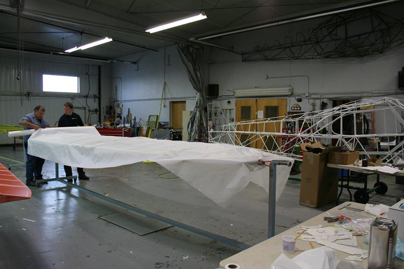 Baker Air Service duo, father-son Roger and Darin Meggers cover a wing with polyester fabric from Consolidated Aircraft Coatings. Photo courtesy of Baker Air Service.