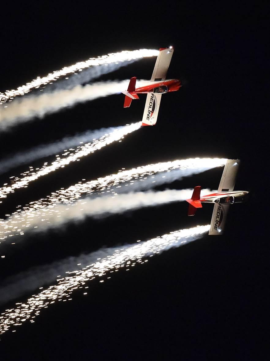Ken Rieder and Jon Thocker with Team Readline dazzle the crowd with fireworks trailing from their Van's RV-8 aircraft during the night airshow at EAA AirVenture in Oshkosh July 27. Photo by David Tulis.
