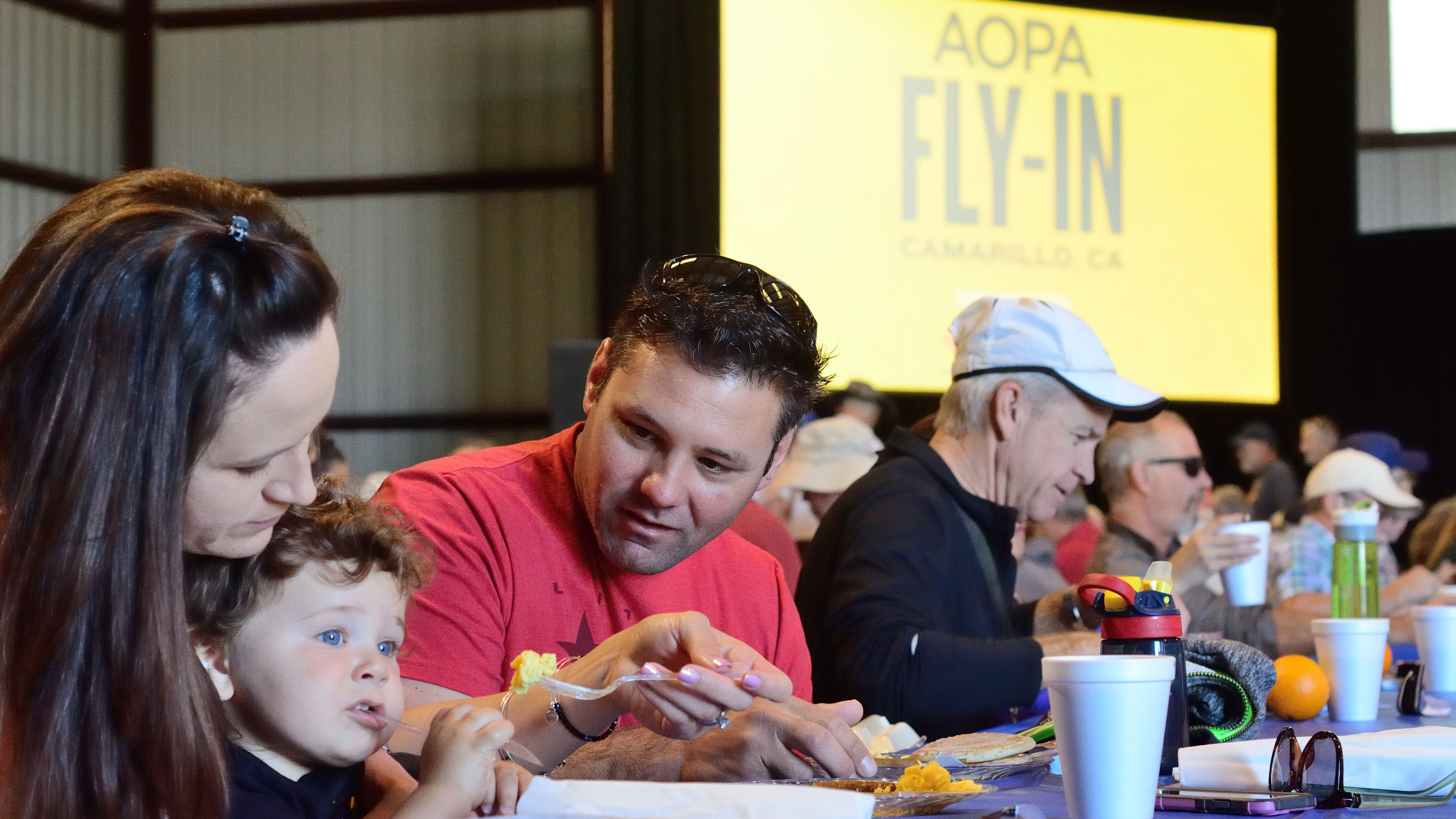 Sarah Bartush; her son, Bradley, 16 months; and husband Chris Bartush enjoy the pancake breakfast Saturday morning. Their family owns Channel Islands Aviation, based at Camarillo. Photo by Mike Collins.