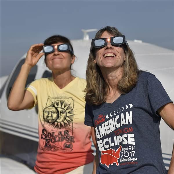 "Cherokee Six pilot Sandy Wirth and her sister Nancy Hunt view the total solar eclipse from the Madras Municipal Airport aircraft camping area where hundreds of aviators and nonaviators alike witnessed the phenomenon in Madras, Oregon. ""This was the most incredible environment,"" said Wirth, who camped out under the stars to make sure she was in the perfect spot. Photo by David Tulis."