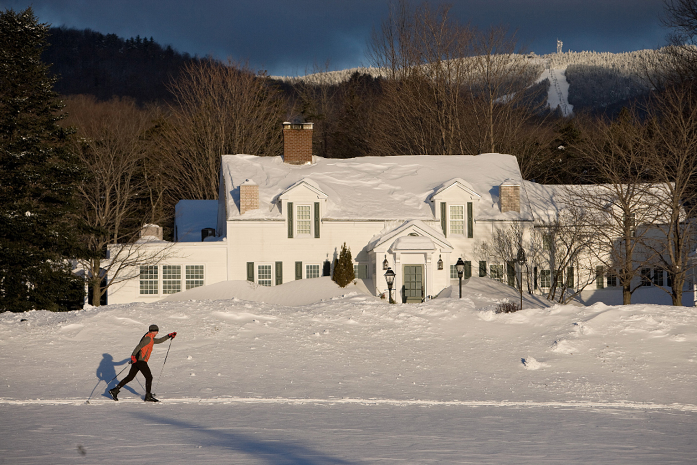 A cross-country skier passes in front of the Hermitage Inn. The Hermitage Club's fully marked and maintained 9-mile trail offers the opportunity to explore Vermont's beautiful Deerfield Valley. Whether you want to challenge your pace on skis or go snowshoeing, the trails are accessible to all. Photo courtesy Hermitage Club.