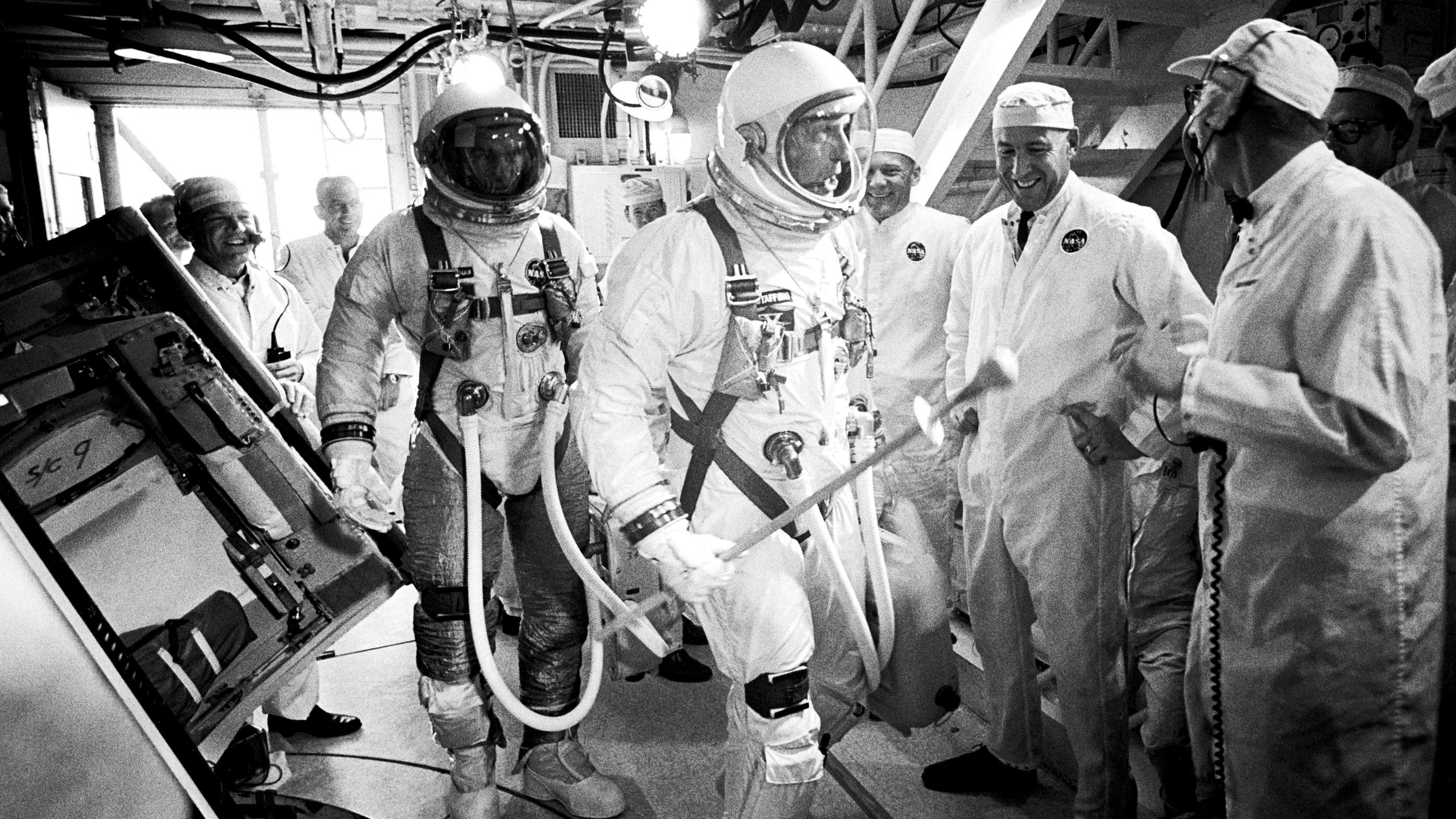 After two postponements, Gemini IXA astronauts Eugene Cernan, left, and Tom Stafford, center, arrive in the white room atop Launch Pad 19 at Cape Kennedy Air Force Station on June 3, 1966. Stafford is presenting a large match to McDonnell Aircraft Corporation's pad leader Gunter Wendt, far right. Photo courtesy of NASA.