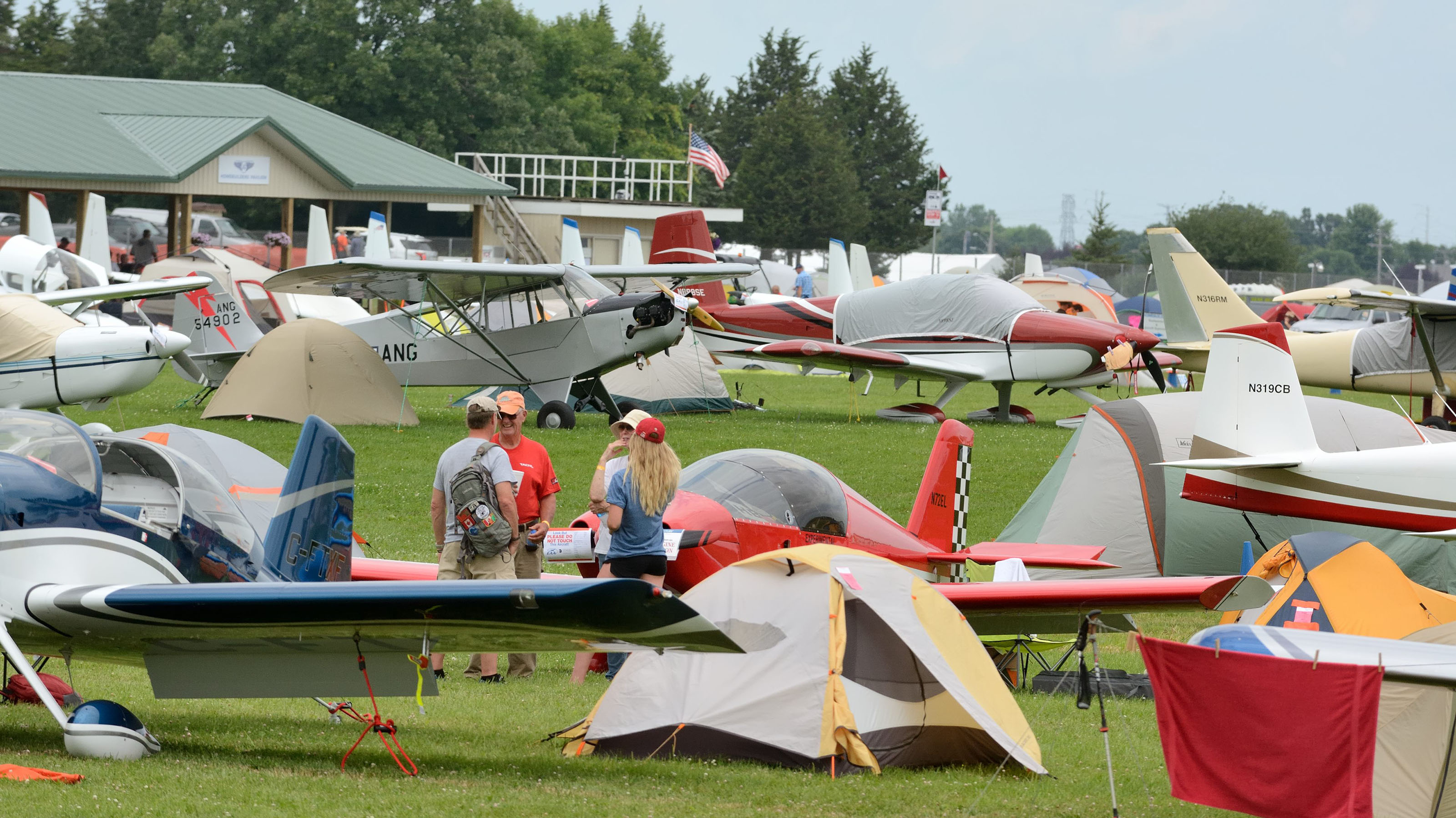 As EAA AirVenture 2017 spools up, attendees talk in one of the aircraft campgrounds. Photo by Mike Collins.