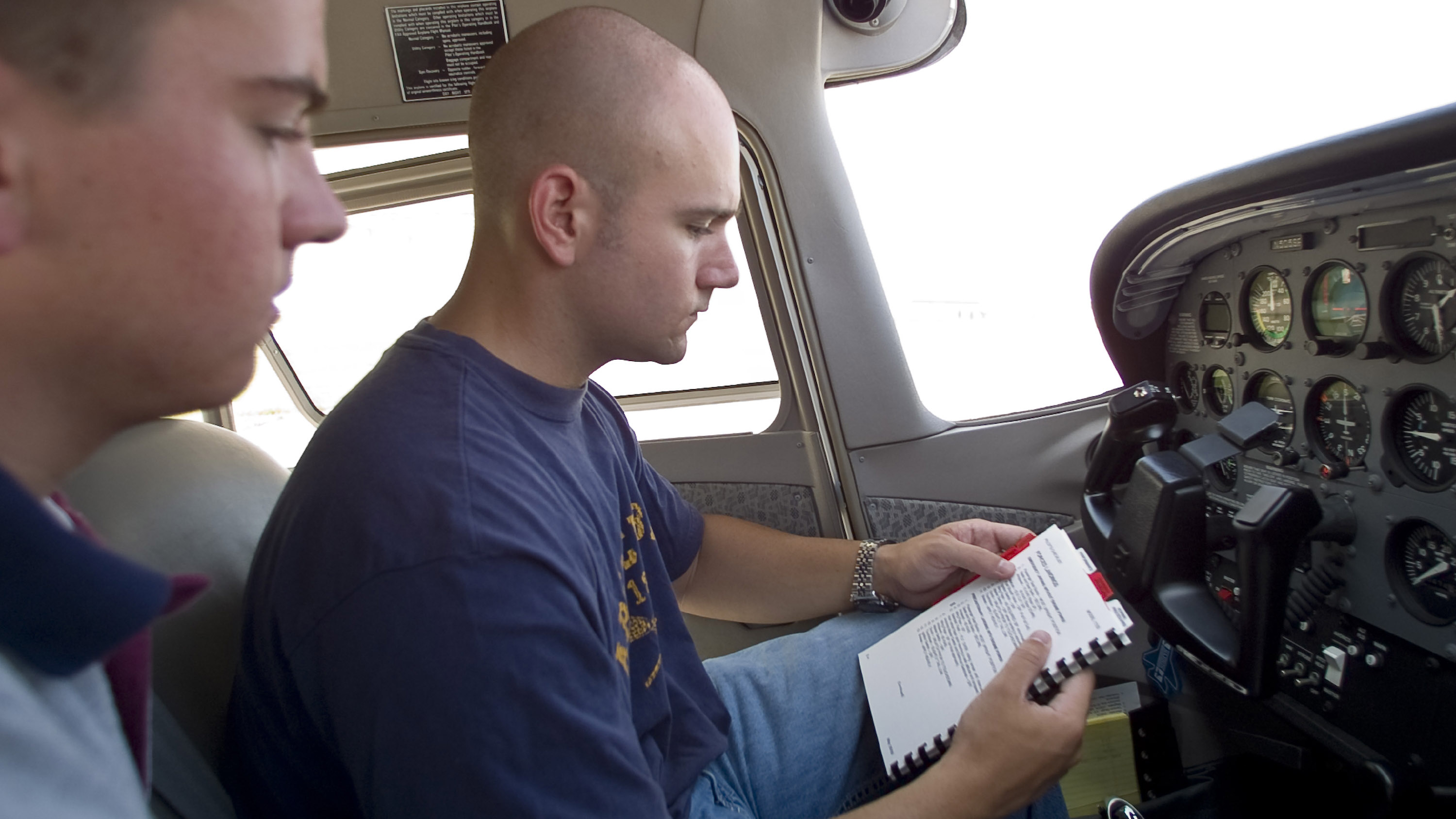A student and his instructor reviewing the emergency checklist in the cockpit of a Cessna 172 Skyhawk.