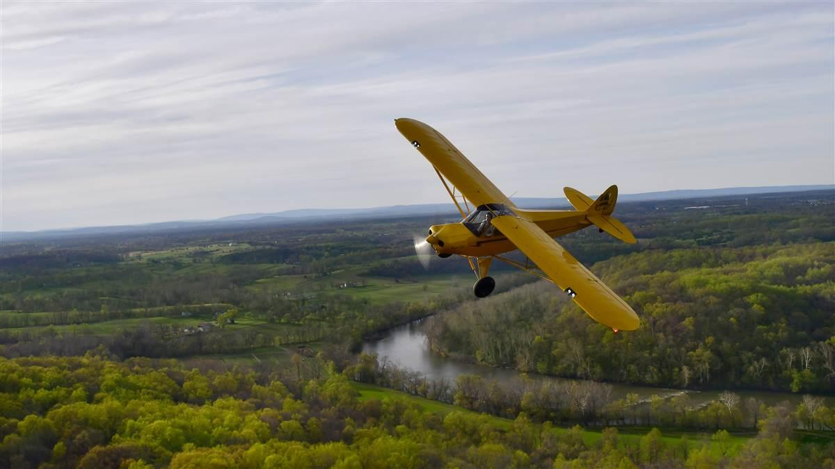 Sunlight illuminates the AOPA Super Cub Sweepstakes aircraft over the mountains and valleys of Maryland, Virginia, and West Virginia. Photo by David Tulis.