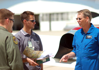 An instructor talks with students at the National Test Pilot School.