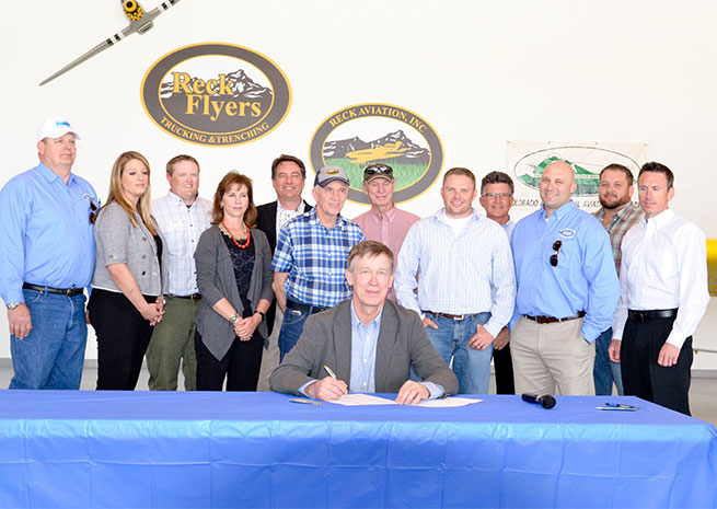 Gov. John Hickenlooper signs Colorado's tower marking law at Reck Aviation, an aerial application business. Photo courtesy of the Colorado Agricultural Aviation Association.